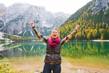 A happy, smiling woman hiker cheers for joy at Lake Bries