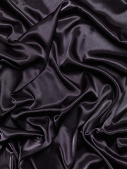 Black shiny silky fabric abstract background