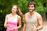 Portrait of cheerful couple running outdoors