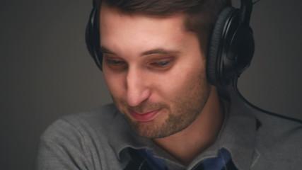 Man listening music in headphones on grey background