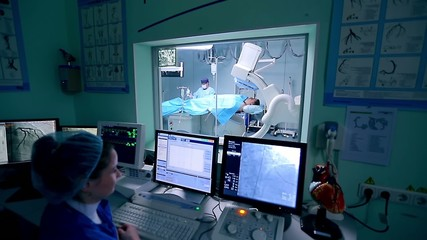 Assistant controls a cardio surgery in front of monitors