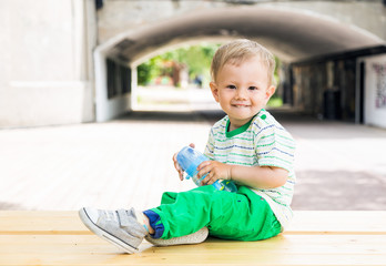Smiley little boy playing on a wood bench