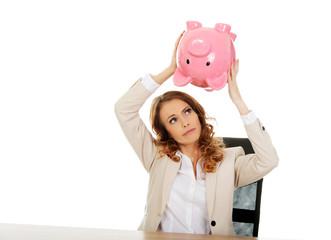 Business woman shaking a piggybank.