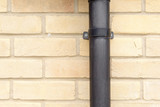 Close up of a black  clamp on a drainpipe poster