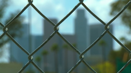 Wide rack focus from chain link fence to downtown Los Angeles.