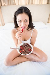 Pretty brunette eating strawberry on bed