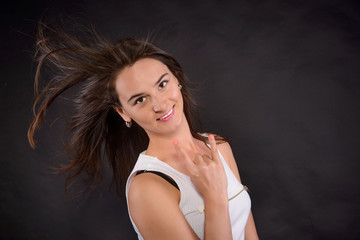 Cheerful brunette girl in the studio on a dark background