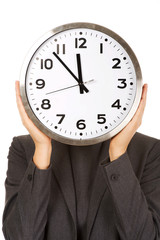 Woman covering face with clock.