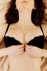 Sexy brunette woman taking off her bra.