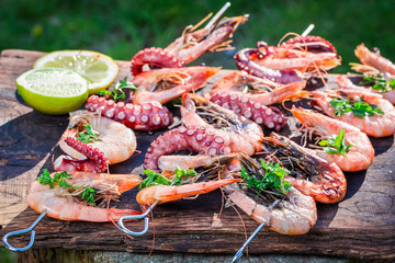 Tasty grilled skewers of seafood with lemon and parsley