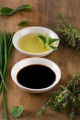 Olive oil, balsamic vinegar and herbs  on wooden background
