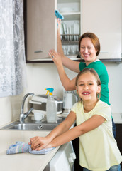 girl and mom tidy kitchen up