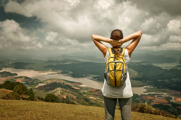 Portrait of happy traveler girl with backpack standing on top,