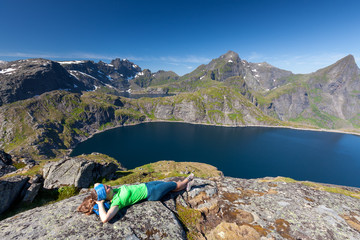 Woman takes rest on top of mountain in Norway
