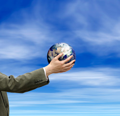 an image of hands holding globe and sky