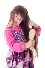 Little girl combing her frizzy hair