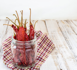 dry chili in bottle on wooden background