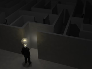 Businessman with bulb  in front of a   mysterious maze