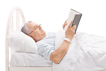 Mature patient reading book in a hospital bed