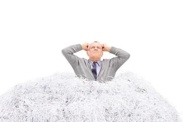 Senior man stuck in a pile of shredded paper