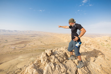 Man standing desert mountain cliff edge.
