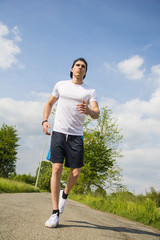 Young man running and jogging on road in country