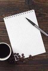 Coffee, opened notebook and pen