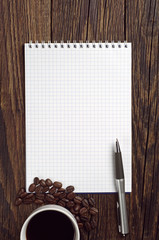 Notepad and coffee on table