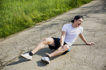 Handsome young man injured while running and jogging on road