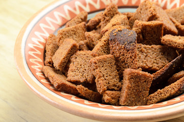 Rye bread croutons in a bowl on a wooden background