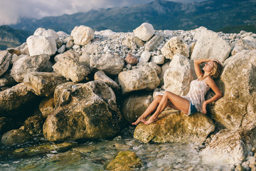 dreamy girl lay on rock beach with mountains background