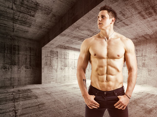 Muscular shirtless young man with jeans, indoors in empty
