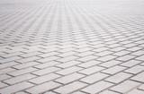 Fototapety Grey brick stone street road. Light sidewalk, pavement texture