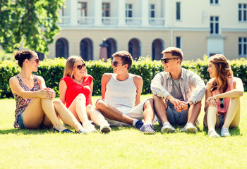 group of smiling friends outdoors sitting on grass