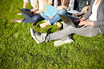 close up of students with laptop sitting on grass