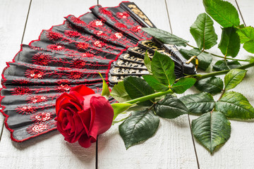 Folding fan and red rose