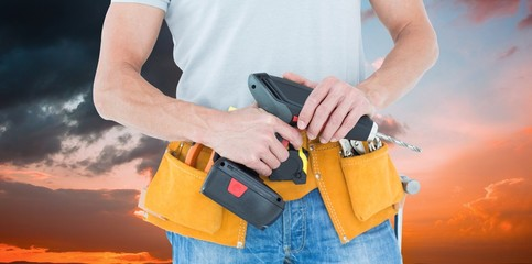 Composite image of repairman holding handheld drill