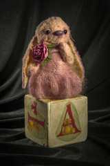 Hare doll in a pink dress on the cube.