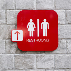 restroom signs with female and male symbol and arrow direction
