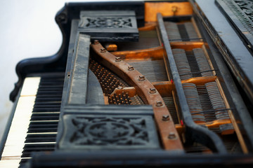 Old piano detail with keyboard, wooden carved ornament and mecha