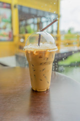 Iced coffee with straw in plastic cup.