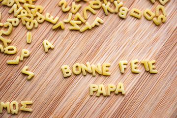 Bonne Fête Papa, écrit avec des petites pâtes, fond bois