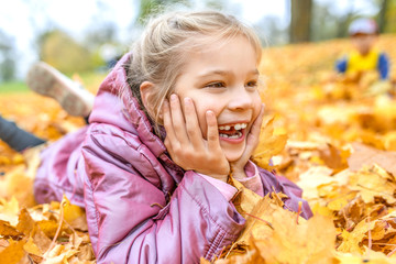 Little girl buried in autumn leaves yellow