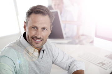 Cheerful man sitting in office and working on desktop