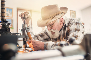 Senior man carving letters into a marble plaque