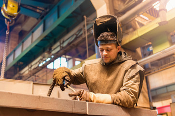 Young man with protective mask in a welding factory