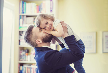 Young father hugging his daughter as he gets home from work