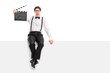 Movie director holding clapperboard seated on a panel