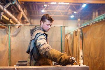 Young man in a factory preparing equipment for welding