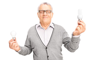 Senior man holding two light bulbs